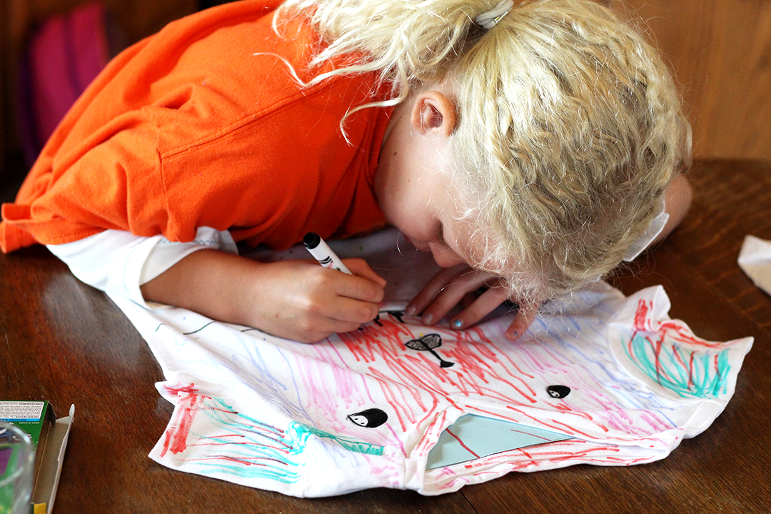 Grandchildren decorate t-shirts with fabric markers